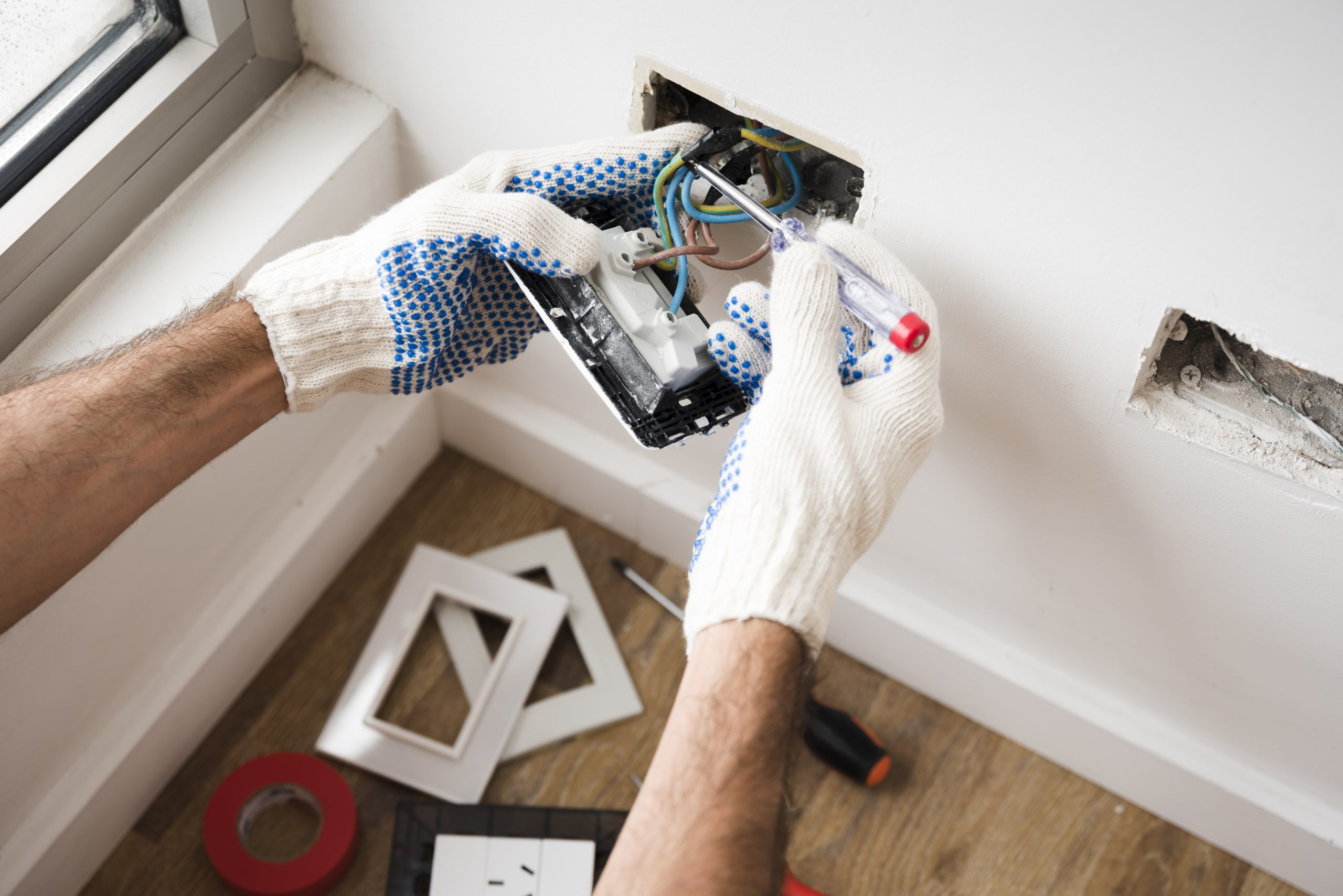 electrician-s-hand-installing-power-socket-home