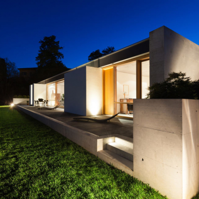 Modern house in cement, view from the garden, night scene